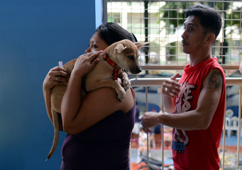 A flood victim holds a meal stub as she carries her dog at an evacuation centre for people displaced by flash floods in Marikina