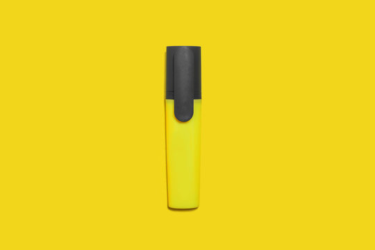 new yellow bright plastic marker lying on a yellow background. concept of office supplies