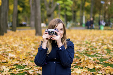 Young pregnant girl holds a camera and takes a picture. Autumn P