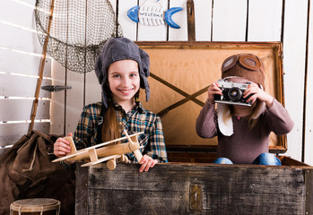 two little girls-pilots in big wooden chest playing camera and wooden plane