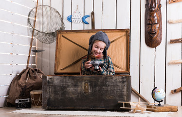 little girl in pilot hat in wooden chest with rarity camera