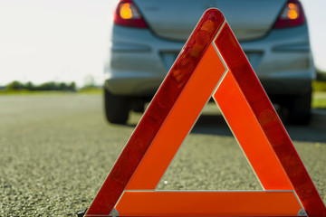 A warning triangle on the background of a damaged car