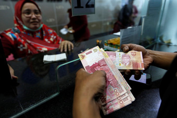 A customer holds Indonesian rupiah bank notes at a money changer in Jakarta