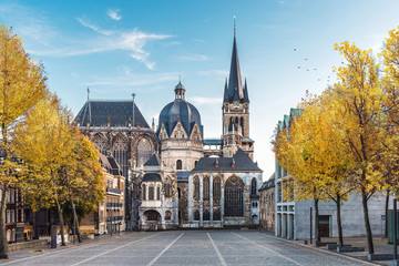 Foto auf Acrylglas Historisches Gebaude German cathedral in Aachen during fall with yellow leafs at trees with blue sky