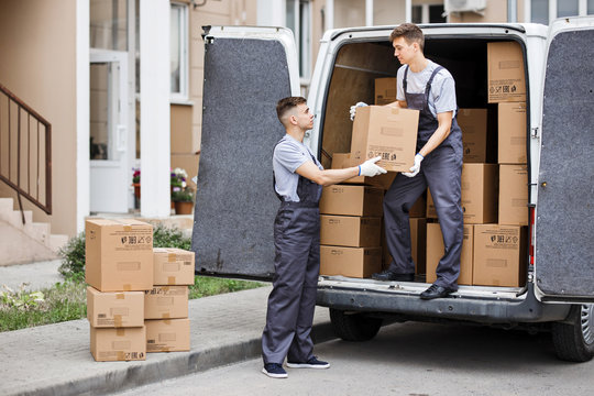 Two young handsome movers wearing uniforms are unloading the van full of boxes. House move, mover service.
