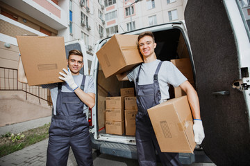 Two young handsome smiling workers wearing uniforms are standing in front of the van full of boxes holding boxes in their hands. The block of flats is in the background. House move, mover service.