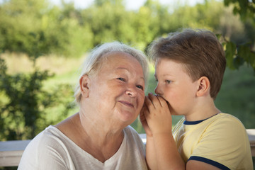 Boy whispering to grandma in summer outdoors garden, grandkid and grandmother lalking