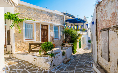 Small narrow street of Greek village of Lefkes with houses made of stone with small yard outdoors, Paros island