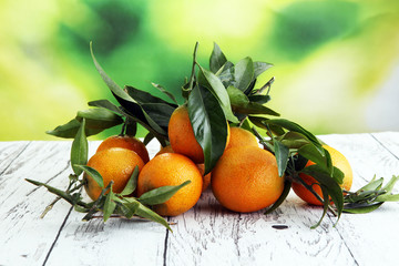 Tangerines with leaves on wooden background. Mandarins Rustic style