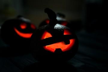 Halloween pumpkin Jack-o-lanterns on the dark wooden background