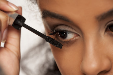 portrait of a young dark-skinned woman applying mascara on a white background