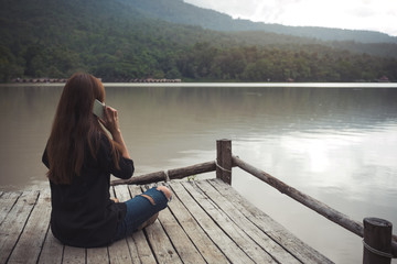 Closeup image of a woman sitting and talking on mobile phone on an old wooden pier by the river with sky and mountain background