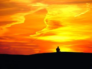 Man on sunset background and orange sky