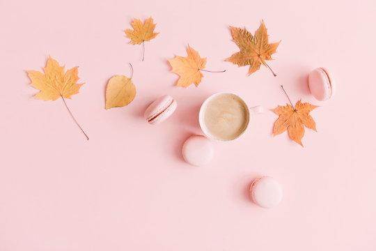 Autumn trendy composition. Cup of coffee and macaroon, dry leaves and flowers on pastel pink background. Flat lay, top view, copy space