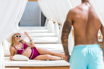 girlfriend looking at boyfriend and lying at sun lounger