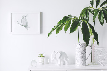 Stylish and modern white interior with mock up frame , elephant figures., tropical leaf and cacti White concept of cupboard shelf.