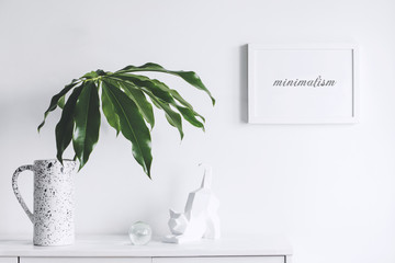 Minimalistic concept of white home interior whit copy space, tropical leaf and cat figures. Scandinavian white cupboard concept.