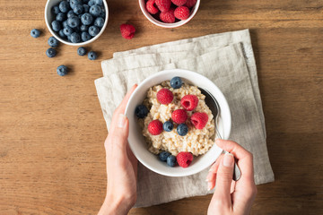 Eating oatmeal porridge for healthy breakfast. Female hands holding bowl with oatmeal porridge and fresh berries. Concept of healthy lifestyle and healthy eating