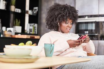 Frau mit Smartphone hört Musik und liest Chat Nachrichten