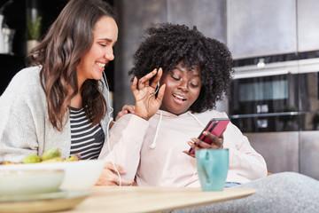 Zwei lachende Frauen hören Musik und singen