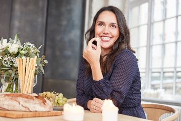 Lächelnde Frau isst Käsewürfel beim Abendbrot