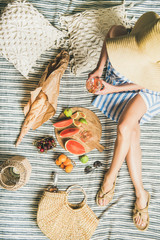 Aluminium Prints Picnic Summer picnic setting. Woman in linen striped dress and straw sunhat sitting with glass of rose wine in hand, fresh fruit on board and baguette on blanket, top view. Outdoor gathering or lunch concept