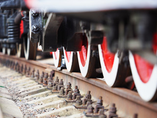 Old steam train wheels approaching, close-up, view from a railway. Black and red. Rails and sleepers