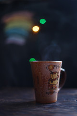 a cup on the wooden background . Christmas bokeh