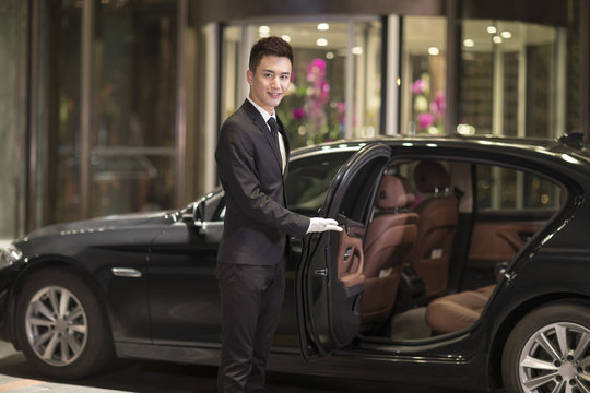 Chauffeur opening car door for passenger