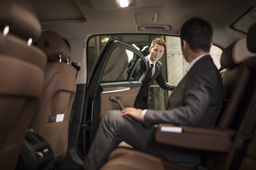 Successful businessman sitting in car back seat