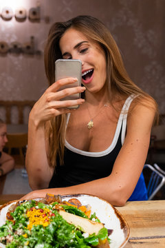 Cheerful woman taking selfie in cafe