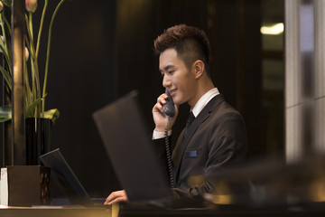 Cheerful hotel receptionist talking on the phone