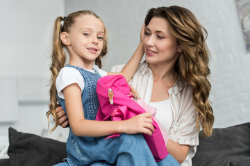 portrait of mother and little daughter with pink backpack on sofa at home