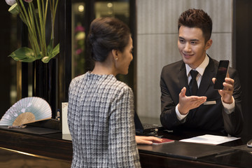 Elegant woman checking into hotel