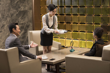 Young waitress serving coffee to business people