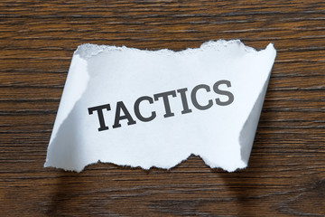 Tactics - an inscription on a piece of white paper, a scroll. Concept of a plan, thought out, warning.