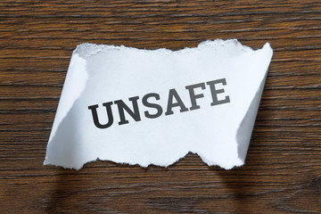 unsafe - an inscription on a piece of white paper, a scroll. The concept of violation of safety precautions, irresponsibility, clumsiness.