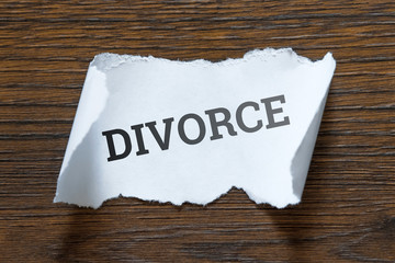 Divorce - an inscription on a piece of white paper, a scroll. The concept of the division of property, the end of love, betrayal, custody of children, the end of marriage.