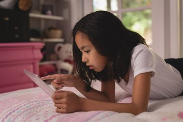 Girl using digital tablet in bedroom