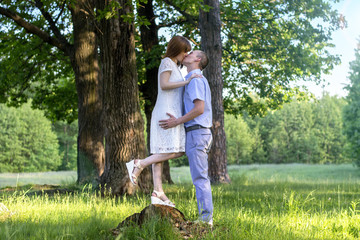 Beautiful Couple In Love Embracing Each Other In Nature. Portrait Of Happy Woman And Handsome Young Man In Stylish Clothes Hugging And Enjoying Date Outdoors. Romantic Relationship.