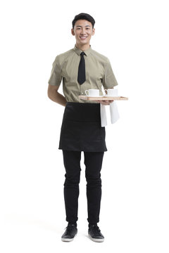 Young waiter holding cups of coffee