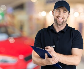 Delivery man with clipboard on office background