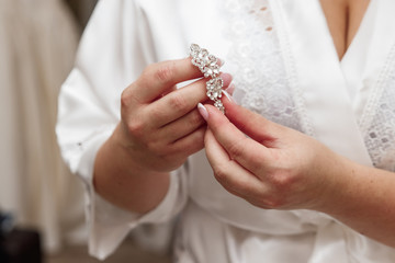 Elegant bride holding silver earrings. Tender hands with jewelry.
