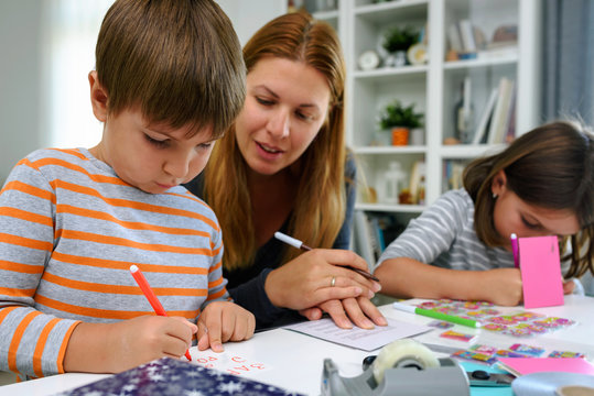 Mother together with kids at home writing birthday cards. Early education