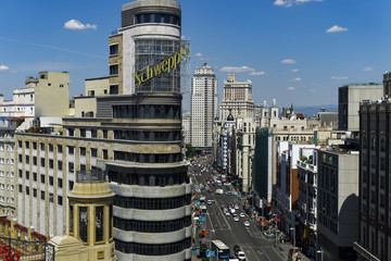 Madrid, Spain Gran Via panoramic view. Day traffic view of main shopping street with Carrion building advertisement in the centre of Madrid.
