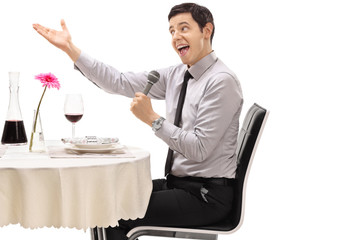 Young man sitting at a restaurant table and singing on a microphone