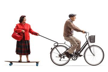 Elderly man on a bicycle pulling an elderly woman on a longboard
