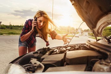 Attractive blonde in front of her car broken down car, assistance concept. Upset woman emotionally reacting on overheated car standing on the roadside with the open hood.
