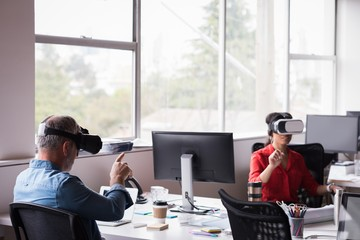 Office colleagues experiencing virtual reality headset at desk