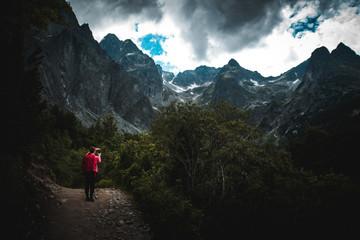 Dark photo of female tourist in mountains, dark sky in background